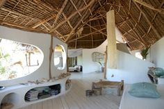 Organic boho home of Marzia Chierichetti. Beautiful white walls, natural curves, timber thatched roof. Love the bay window shelving and raw chic vibe.