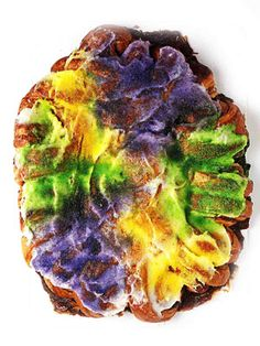 Introduced by French settlers in the 1600s, New Orleans's traditional King Cake is sweetened, yeasted bread stuffed with a filling (cinnamon and cream cheese, say, or praline), shaped into an oval ring, topped with white icing, and garnished with purple, green, and gold sanding sugars.