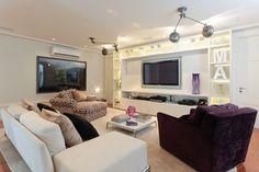 O home theater com 33 m² foi planejado pela arquiteta Paloma Cardoso e proporciona aconchego e conforto para a família, durante as sessões de TV. O ambiente conta com estofados superconfortáveis, além de painel para a TV e estante com nichos decorativos e iluminados. No forro, caixas, pontos de luz embutidos e duas luminárias estão acomodados