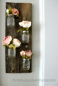 mason jar flower holder - hose clamps on an old piece of distressed wood to hold the mason jars on.