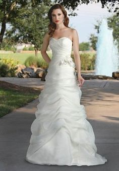 Strapless organza wedding gown featuring sweetheart neckline, pick up skirt and and beaded fabric flower detail at the side