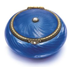 A Fabergé jewelled enamel pill box, workmaster Michael Perchin, St Petersburg, 1899-1903, of circular cushion form, the surface of translucent sky blue enamel over swirling wavy engine-turning, the lid centred with a collet-set rose-cut diamond and bordered with chased gilt laurel, diamond-set thumbpiece.