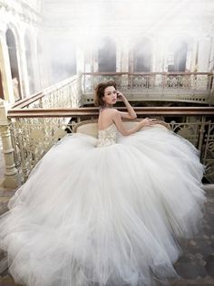 Huge tulle skirt and sparkled strapless top, opened back, seated in a chair over a balcony