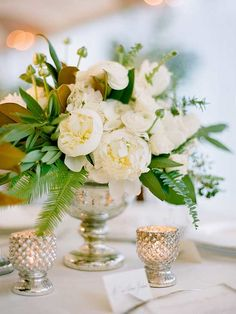 This classic all-white arrangement photographed by Jose Villa stuns as a centerpiece. Pair a grouping of lush white peonies with wisps of greenery like ferns, and display in a mercury glass vase for a luxurious feel!/