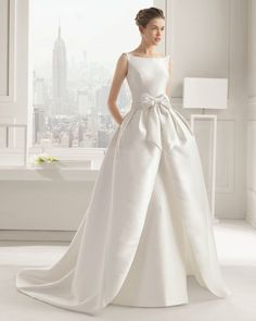 sleeveless wedding dress with boatneck collar and bow at waist