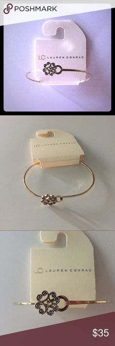 "LC Lauren Conrad Goldtone Bangle Bracelet Delicate goldtone bracelet with heart/flower design. Has hook and closure for easy on and off. A little bit wider than 2.5"" at widest. Design is a little off-center. Made this way because the way the closure is set. I have several of these available. I purchased to give as gifts and then went in another direction. LC Lauren Conrad Jewelry Bracelets"
