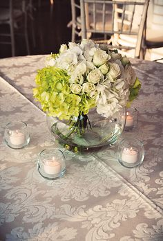 ivory damask tablecloths, centerpieces of white and green hydrangeas and ivory roses surrounded by votive candles. Jessica Horwitz Photography.