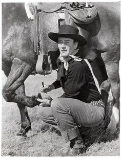John Wayne picking out his horses hooves.
