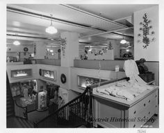 Black and white photographic print of the interior floors at the J.L. Hudson and Company Department Store. Girls flannel pajamas are displayed next to a cash register in the foreground; the upper floor also features ladies hosiery, and men's undergarments. Staircases leading to the lower floor are also visible. Ladies housecoats in various colors and styles are sold on the floor below.