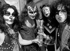 Creem photo shoot of KISS holding cans Boy Howdy Beer (1974)