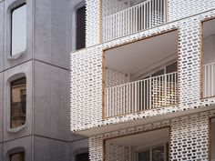 Balconies extending from the front of this apartment block in Paris are framed by white concrete screens featuring a perforated pattern that resembles brickwork.