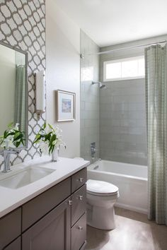 This small guest bathroom packs in a lot of style, with a fully tiled tub-shower combo and a decorative backsplash that extends to the ceiling for added drama. Glass cabinet hardware gives the space sparkle.