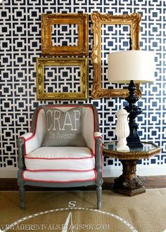 I LIKE THE GUILDED FRAMES AGAINST THE DEEP NAVY BLUE AND WHITE WALL, BERGERE CHAIR & THE DEEP NAVY BLUE LAMP