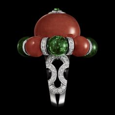 "CARTIER. ""Flamboyant"" ring - platinum, one 30.19-carat coral bead, four coral beads totalling 13.47 carats, four emerald beads from Zambia totalling 14.28 carats, cabochon-cut emerald, onyx, black lacquer, brilliant-cut diamonds. Étourdissant Cartier 2015"