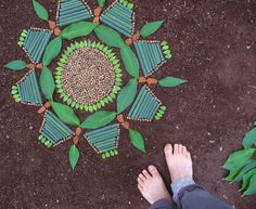 Bare feet on soft earth while creating mandala art design grounds the body.