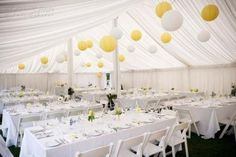 Yellow lanterns with a white marquee and rectangular tables