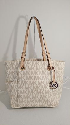 Michael Kors East West Signature Vanilla Tote Bag. Get one of the hottest styles of the season! The Michael Kors East West Signature Vanilla Tote Bag is a top 10 member favorite on Tradesy. Save on yours before they're sold out!
