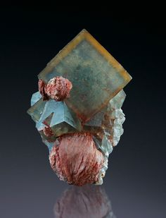 Fluorite, Baryte Photo Copyright © martin gruell  - This image is copyrighted. Unauthorized reproduction prohibited. Locality: Hameda Quarries (Lhamda Mine), Jorf, Er Rachidia Province, Meknès-Tafilalet Region, Morocco Fluorite with Baryte. 9,5 x 5,5 x 4cm. Hameda, Sidi Kacem Prov., Morocco. The main crystal is up to 38mm on edges, it shows blue internal colour with yellow outer zones. The reddish Baryte ate the base is about 28mm in diameter. Material and foto Martin Gruell.