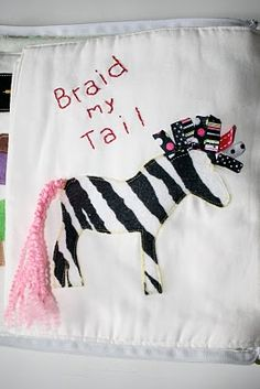 A quiet book page where you braid the zebra's tail, rather than a little girl's hair. I like it.