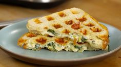 Recipe with video instructions: The tastiest way to eat your greens is by stuffing them into a buttery, cheesy sandwich. Ingredients: 2 Tbsp cream cheese, softened, ¾ cup shredded Swiss cheese, ¾ cup shredded Gruyere, ¼ cup grated Parmesan, Olive oil, for sautéing and brushing, ½ clove garlic, thinly sliced, Crushed red pepper flakes, 3 cups fresh spinach, ⅓ can of artichoke hearts (about 4 hearts), roughly chopped, White crusty loaf of bread, cut into 1-inch slices, Salt, to taste