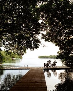 A dock just resting above the water's surface...two chairs for an intimate getaway