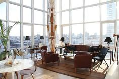 """A 270-degree view of Brooklyn and Manhattan out of 20-foot windows will make any room seem light and airy,"" say designers Porter and Hollister Hovey of this breathtaking space. ""We strove to accentuate the architecture even further with furniture that seemed to float — Børge Mogensen armchairs, an old faux-bamboo campaign chair, an Eero Saarinen tulip table."""
