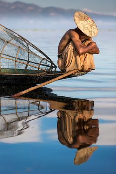 A Burmese fisherman rests at the point of his boat on an Inle Lake morning in Myanmar.