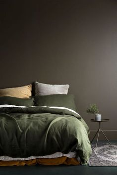 Love this muddy brown feature wall and olive green bedding. Such a warm palette!