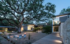 """""""The lone valley oak in some ways defined the shape of the house,"""" says landscape architect Bernard Trainor. The structure wraps around the century-old tree, forming a courtyard with a series of fiber-cement chairs by French designer Julia von Sponeck. Architecture Courtyard, Architecture Design, Outdoor Spaces, Outdoor Living, Outdoor Decor, Landscape Lighting, Landscape Photos, Outdoor Landscaping, Curb Appeal"""