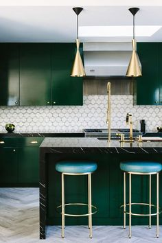 Midcentury-modern kitchen with herringbone tile floor, brass pendants, glossy green lacquer cabinets and a hex tile backsplash.