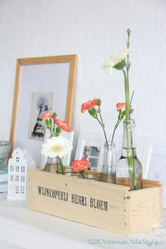 // wooden shallow box. simply glass jars/bottles. bright flowers.