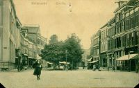 Gezicht vanaf de Grote Markt op het begin van de Melkmarkt, ca. 1930. Links staat op de stoep rond De Harmonie (Grote Markt 13A) nog een hekwerk. Het hoge pand aan de zuidzijde van de Melkmarkt, behoort toe aan de firma Tijl, uitgever van de Zwolse Courant. Uiterst rechts zijn de panden Grote Markt 12 en Melkmarkt 2 (met hijsbalk) en volgende te zien. Op nr. 2 was het kantoor van uitgeverij Tjeenk Willink gevestigd. De dame op de voorgrond loopt onverveerd over straat.