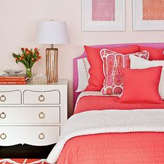 Warm Coral Hues | Bright, warm colors in fabrics and accesories really pop against white walls in this bold bedroom.
