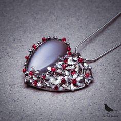 Poslední+Mohykán+-+náhrdelník+Autorský+cínovaný+náhrdelník+se+skleněným+šedým+kabošonem+s+metalickým+efektem+ve+tvaru+kapky.+Polovinu+přívěšku+vyplňují+drobné+kytičky+se+skleněnými+červenými+středy.+Vše+doplňují+kuličky+z+cínu.+Celý+šperk+je+ruční+práce,+je+vytvořen+bez+bižuterních+komponentů.+Šperk+je+zavěšen+na+hadím+řetízku,+délka+závěsu+42+cm...