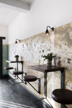"""Le design d'intérieur réalisé par le cabinet d'architecture Technē, du bar The Nelson est inspiré de son emplacement de Bayside à St Kilda et de son offre principale de rhum. L'objectif était de créer un lieu décontracté, un vrai pub local. La caractéristique principal du bar se retrouve dans le bois recyclé des docks et qui donne une ambiance maritime, ainsi qu'une fresque peinte à la main, représentant la mythique créature de mer """"Le kraken""""."""