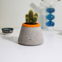 A stunning concrete planter with bright lining Add some greenery to your home or office with this unique handmade concrete planter. Great for small plants and can be used as vase, it is fully watertight. Each concrete planter is handmade and will look completely unique. Inside lining