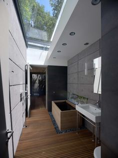 luxury bathroom with wooden floor and natural stone combined with concrete wall including white wash basin featuring transparent glass skylight