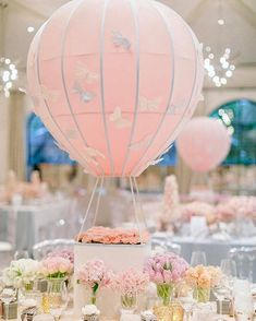 These baby pink hot air balloons with florals surround the base centerpieces were custom designed for a baby shower. Feminine and pretty in every way - Aliana and Celio added additional butterflies for that special touch! Our clear Naples dining chairs enhanced the design. (Planner/Design: @alianaevents Design/Rentals: @revelryeventdesign Florist: @celiosdesign)