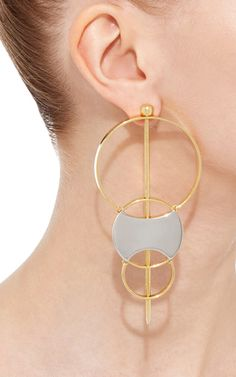 These polished gold **Monica Sordo** drop earrings feature a optional bar that strikes through the center of overlapping rings that decrease in size.