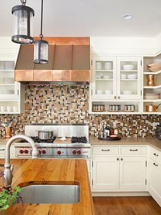 Fuse your kitchen's palette with a multicolor backsplash. The dark chocolate, neutral, and blue tiles unify the earthy colors found throughout this home's cabinetry and countertops for enduring appeal./
