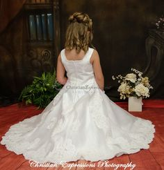 Full length satin and organza heavily beaded communion gown. Sleeveless with pearl accented neckline with organza layer skirt and lace applique and pearl beading. Fully lined This first communion dress is available exclusively at Christian Expressions and our authorized websites