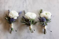 White ranunculus and thistle buttonholes, tied with twine.