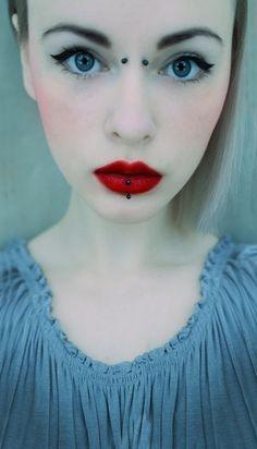 Cyber bites on lips and bridge piercing between eyes.