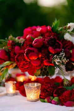 Romantic ruby red peonies paired with the soft glow of lit votives, is a beautiful combination for any elegant reception.