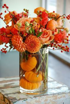 fall bouquet with dahlias, roses, orange ranunculus, bittersweet, and pumpkins
