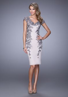 Bold cocktail satin dress with sheer lace capped sleeves. The dress has lace embroidery down the sides and is encrusted with rhinestones. Low V open back with small back slit. Back zipper closure.  Evening Collection Size Chart B.