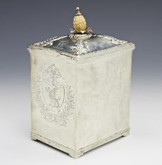 A George III silver tea caddy by Edward Darvill, London circa 1760 -  Of plain square form, the hinged cover embossed with bead and leaf decoration to an applied gadrooned rim, with an ivory pineapple finial, armorial coats of arms and crested, height 15cm, weight 11.5oz.