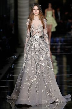 Couture Spring/Summer 2016 Sheer long sleeve ball gown in greige tulle, ornamented with shimmering flowers in 3D