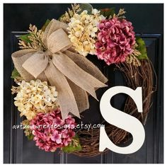 Cranberry pink and cream hydrangeas blend together beautifully with a double burlap bow... beautiful wreath for any season of the year!  Pictured with a classic style monogram in cream, choose the initial monogram you would like to make it personal. The grapevine wreath is 18 in diameter. Flowers, bow, and monogram make it approximately 20 in diameter.  Each flower, letter and bow is wired and glued to the wreath for optimum durability