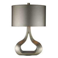 The designer of this lamp took a traditional silhouette and turned it into a pleasing contemporary shape by flattening the base, removing the middle portion, and giving it an oval shade. The silver leaf finish coordinates with the metallic silver faux leather shade which has a silver liner.